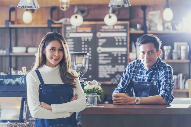 Porträt des asiatischen jungen kleinunternehmers mit kaffeestube vor gegenstange, unternehmer und start