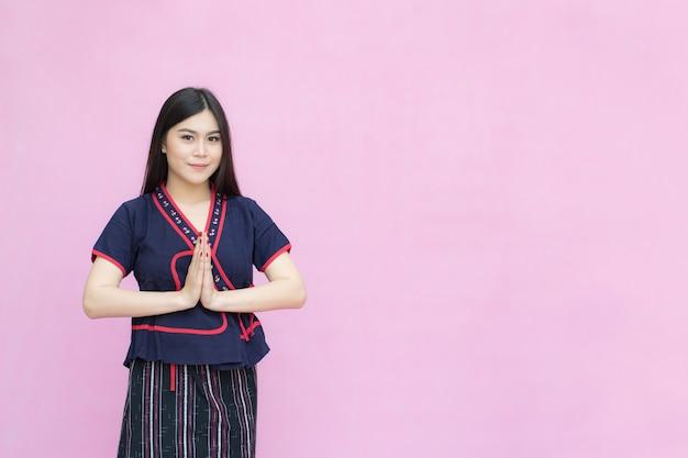 Porträt des asiatischen jungen mädchens im traditionellen thailändischen kleid, das betet