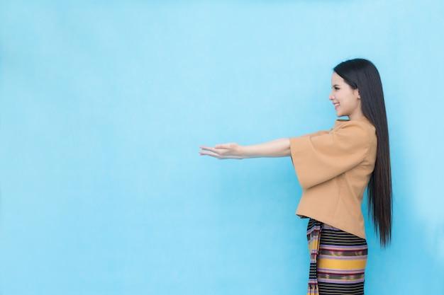 Porträt des asiatischen jungen mädchens im traditionellen thailändischen kleid zeigt leeres zeichen