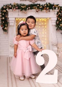 Porträt des asiatischen jungen und der frau, die an nummer zwei umarmen