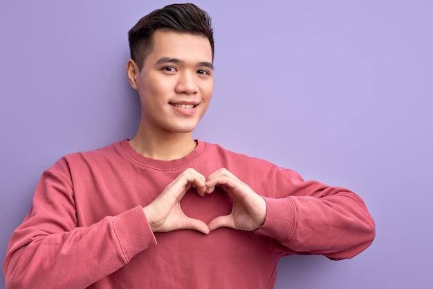 Porträt des asiatischen kerls, der liebe an der kamera ausdrückt