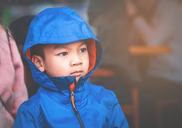 Porträt des asiatischen kinderjungen in der blauen winterkleidung