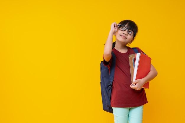 Porträt des asiatischen kinderstudenten, der buch mit gläsern hält und oben auf gelb schaut
