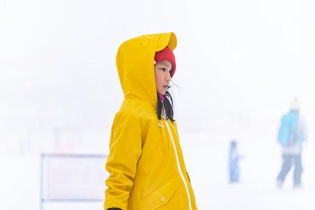 Porträt des asiatischen kindes gril in der gelben winterkleidung