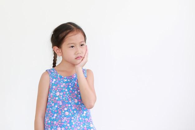 Porträt des asiatischen kleinen kindermädchens, das hand auf kinn und wange berührt, lokalisiert auf weiß