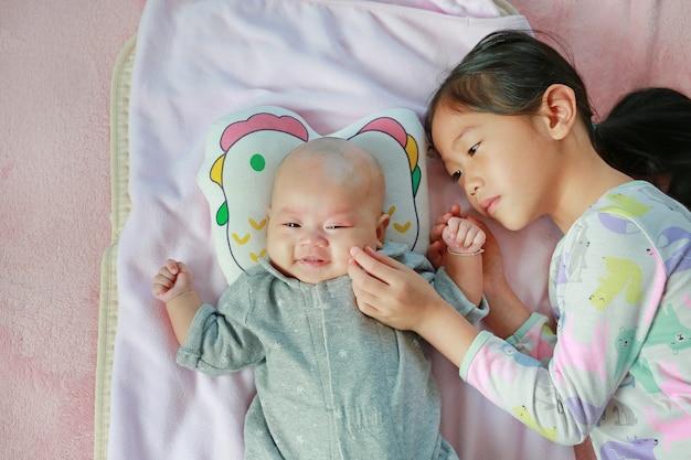Porträt des asiatischen kleinen kindermädchens, das mit ihrer schwester spielt, die auf bett liegt