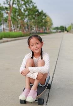 Porträt des asiatischen kleinen mädchenkindes, das auf einem skateboard auf der straße sitzt