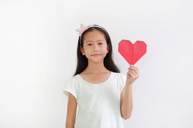 Porträt des asiatischen kleinen mädchenkindes, das rotes herzzeichen auf weißem hintergrund hält