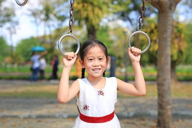 Porträt des asiatischen kleinen mädchens, das auf gymnastikring auf spielplatz im freien spielt.