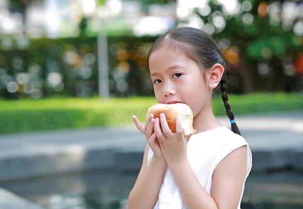 Porträt des asiatischen kleinen mädchens, das brot mit angefüllter erdbeere isst