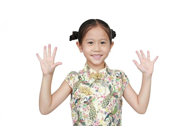 Porträt des asiatischen kleinen mädchens, das cheongsam mit dem lächeln trägt und zwei palmen zeigt, geben fünf isoliert. Premium Fotos
