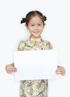 Porträt des asiatischen kleinen mädchens, das cheongsam mit dem lächeln und dem halten des leeren weißen papiers lokalisiert trägt