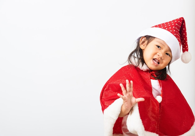 Porträt des asiatischen kleinen mädchens, das im weihnachtsmann lächelt, hat das konzept des feiertagsweihnachts-weihnachtstages
