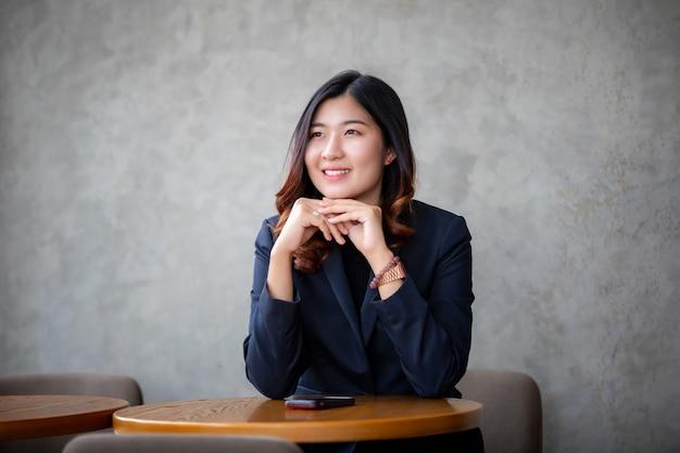 Porträt des asiatischen lächelns der jungen frau betrachtet fenster