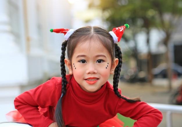 Porträt des asiatischen mädchens des kleinen kindes im weihnachtskostüm in der wintersaison und im guten rutsch ins neue jahr.