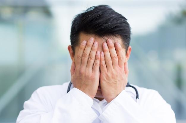 Porträt des asiatischen mannes des arztes, der nach der arbeit müde ist, nahaufnahme foto