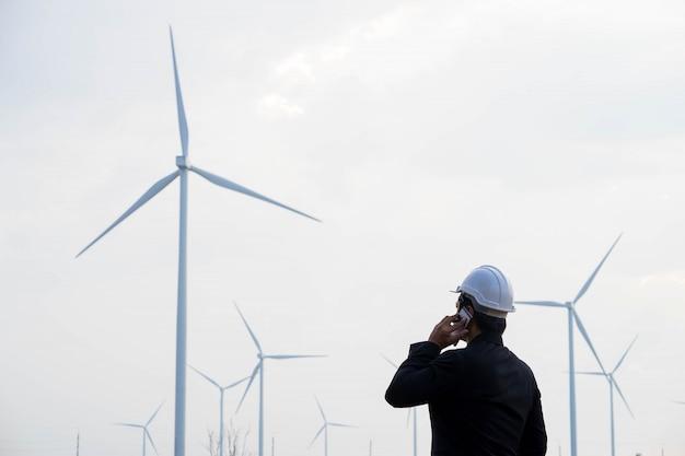 Porträt des asiatischen mannes des geschäfts, der smartphone mit der windkraftanlage im hintergrund hält.