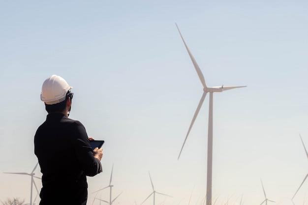 Porträt des asiatischen mannes des geschäfts, der tablette mit der windkraftanlage im hintergrund hält.
