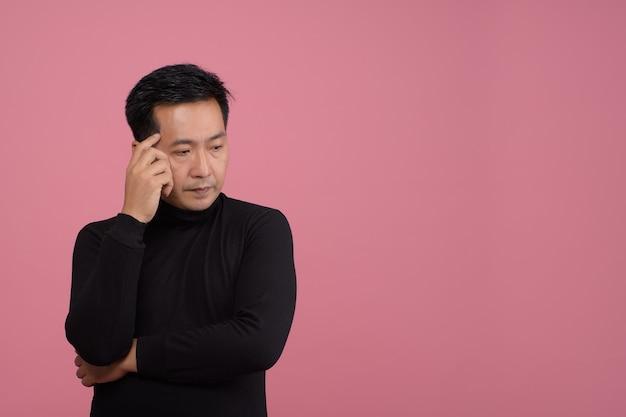 Porträt des asiatischen mittleren mannes, der nachdenklich schwarzen pullover im lässigen stil denkt.