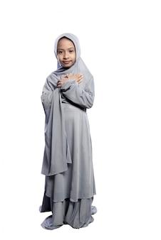 Porträt des asiatischen moslemischen kindes, das hijab stellung trägt