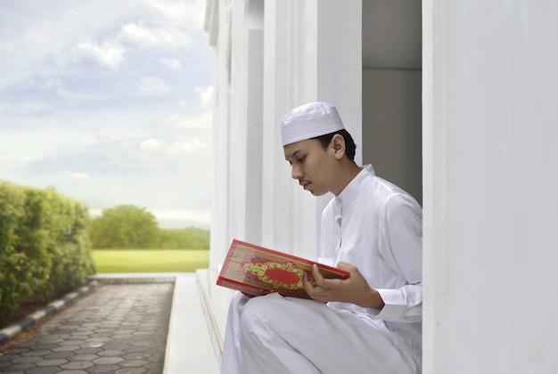 Porträt des asiatischen moslemischen mannes, der den koran liest
