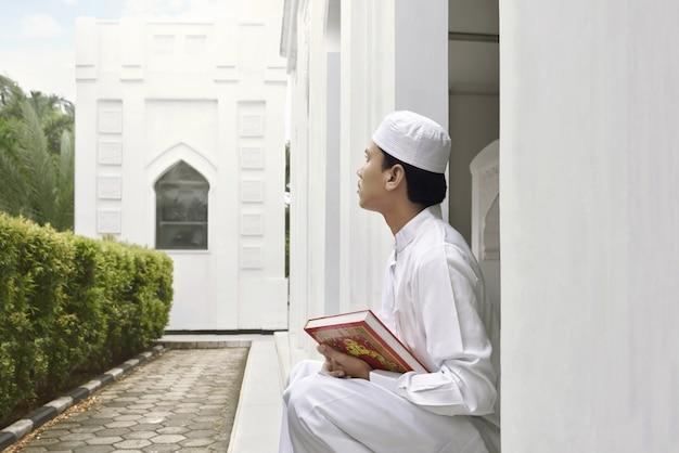 Porträt des asiatischen moslemischen mannes, der quran hält