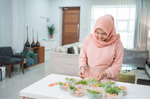 Porträt des asiatischen muslimischen frauenlebensmittelverkäufers, der ihr produkt zu hause küche vorbereitet