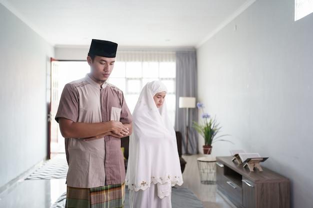 Porträt des asiatischen muslims, der durch faltarm vor einer brust zu hause betet