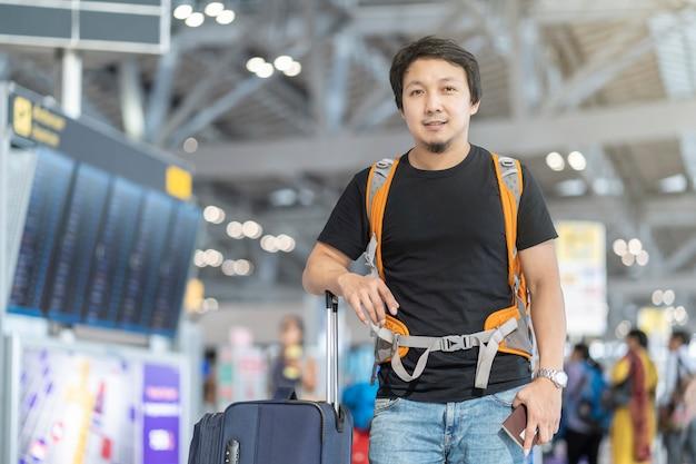 Porträt des asiatischen reisenden mit gepäck mit dem pass, der über dem flugbrett für c steht