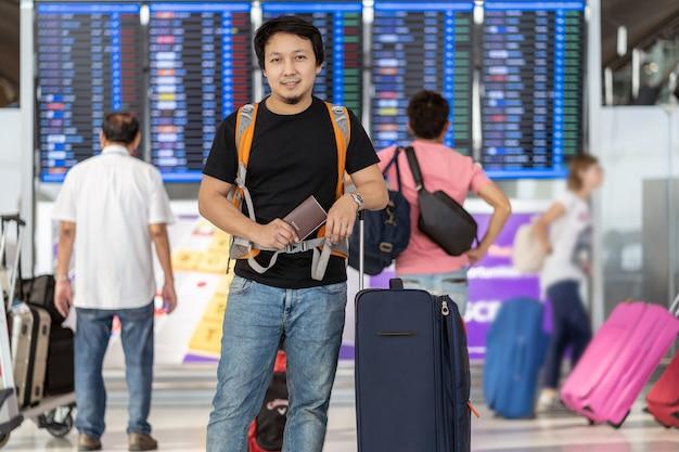 Porträt des asiatischen reisenden mit gepäck mit dem pass, der über dem flugbrett steht