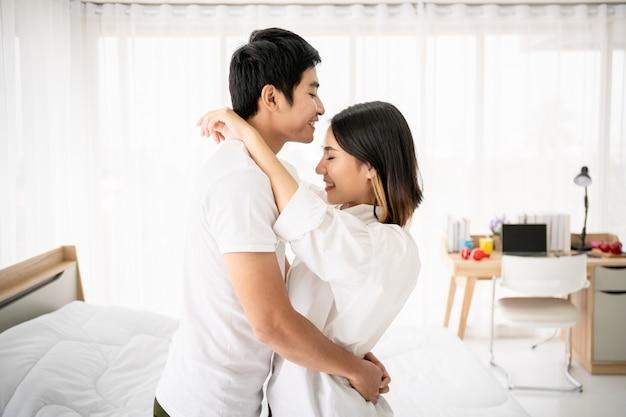 Porträt des asiatischen reizenden paares im schlafzimmer mit natürlichem licht