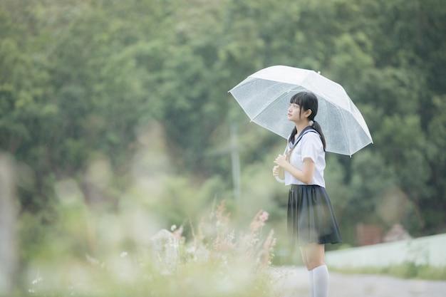 Porträt des asiatischen schulmädchens, das mit regenschirm am naturweg auf regen geht