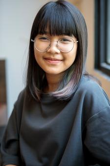 Porträt des asiatischen teenagers, der mit glücksstimmung lächelt