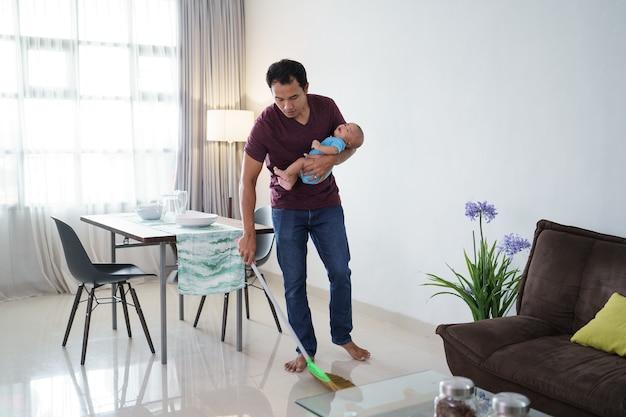 Porträt des asiatischen vaters, der den boden mit besen säubert, während er sein baby trägt