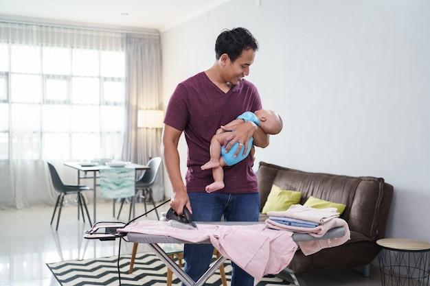 Porträt des asiatischen vaters, der seine kleidung bügelt, während er sein baby auf seiner hand hält