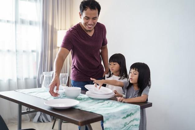 Porträt des asiatischen vaters und der kleinen tochter, die esstisch für abendessen vorbereiten