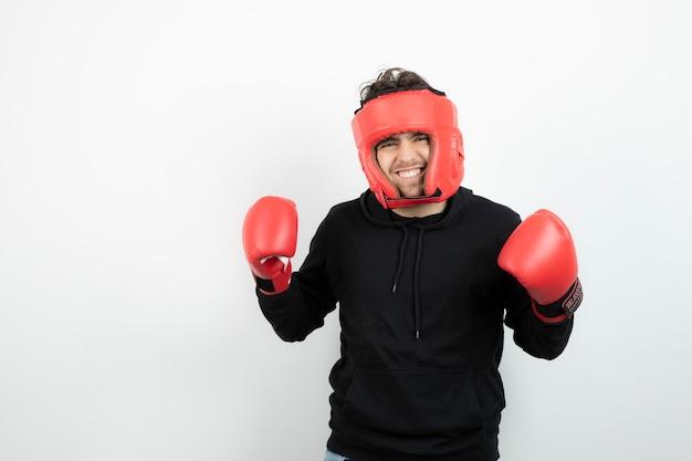 Porträt des athletischen jungen mannes im roten boxhut, der für kampf bereit ist.