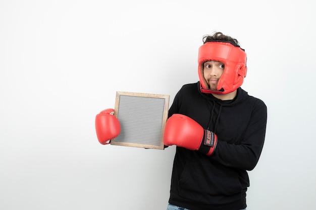 Porträt des athletischen jungen mannes im roten boxhut, der leeren rahmen hält.