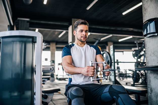 Porträt des athletischen mannes trainierend in der turnhalle, seine armmuskeln und körper verbessernd.
