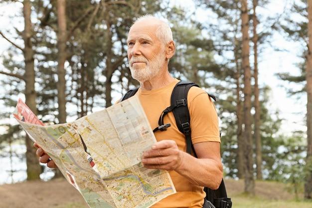 Porträt des attraktiven älteren männlichen reisenden rucksacktourismus unter verwendung der karte, die nach der richtigen route sucht. bärtiger älterer kaukasischer mann, der rucksack trägt und überlegt, wohin er gehen soll, an einer kreuzung im wald