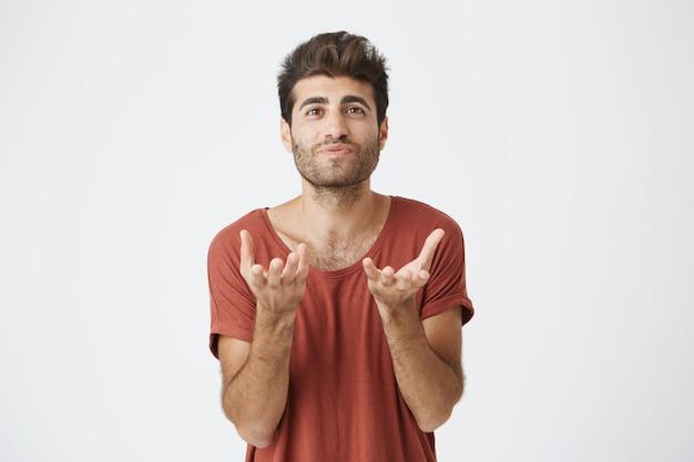 Porträt des attraktiven bärtigen studenten im roten t-shirt, das seine hände streckt. emotionaler mann mit stilvoller frisur, der nicht versteht, was von ihm gewünscht wird