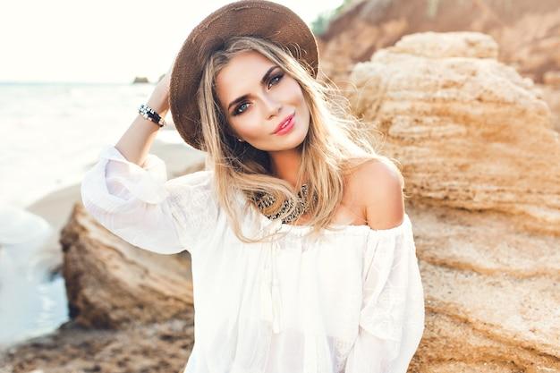 Porträt des attraktiven blonden mädchens mit dem langen haar, das auf verlassenem strand aufwirft. sie lächelt in die kamera.
