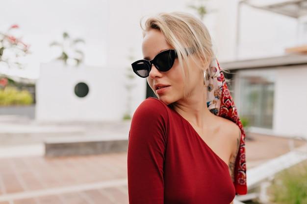 Porträt des attraktiven blonden mädchens mit langen haaren mit accessoires im kopf und brille tragend