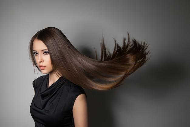 Porträt des attraktiven brünetten modells mit fliegenden perfekten haaren. studioaufnahme