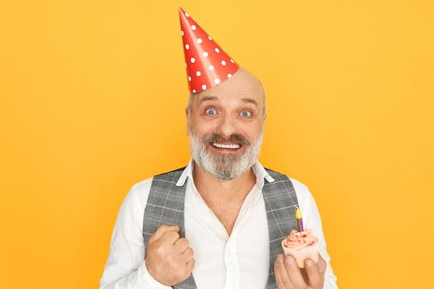 Porträt des attraktiven erfolgreichen älteren bärtigen geschäftsmannes, der kegelhut trägt, der aufregung ausdrückt, geburtstagsfeier genießt, cupcake mit einer kerze hält