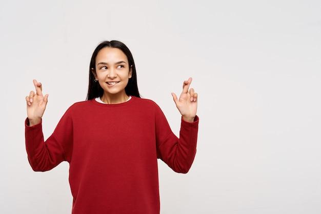 Porträt des attraktiven, erwachsenen asiatischen mädchens mit dem dunklen langen haar. trägt einen roten pullover und drückt die daumen, beißt sich auf die lippe, wünscht sich etwas. nach rechts im kopierbereich auf weißem hintergrund gucken