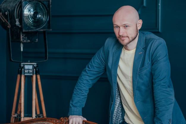 Porträt des attraktiven erwachsenen erfolgreichen kahlen bärtigen mannes in der klage auf blauem hintergrund