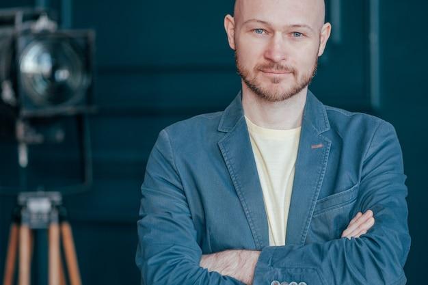 Porträt des attraktiven erwachsenen erfolgreichen kahlen bärtigen mannes in der klage auf dem blauen hintergrund, blogging