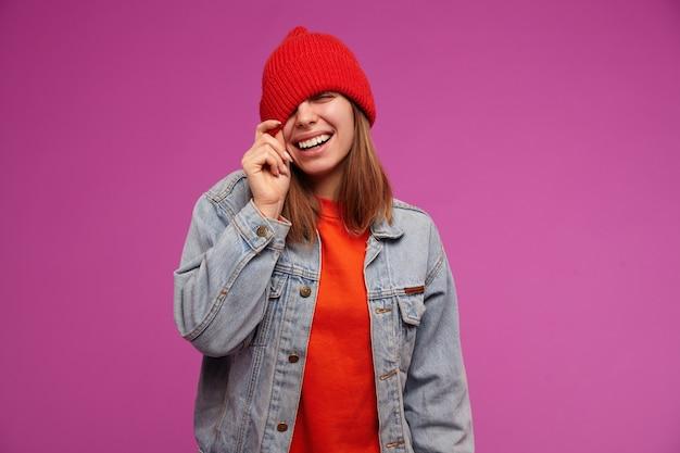 Porträt des attraktiven, erwachsenen mädchens mit brünetten haaren. trägt einen roten pullover, eine jeansjacke und einen roten hut. hut über ein auge ziehen, lächeln. personenkonzept. stehen sie isoliert über lila wand