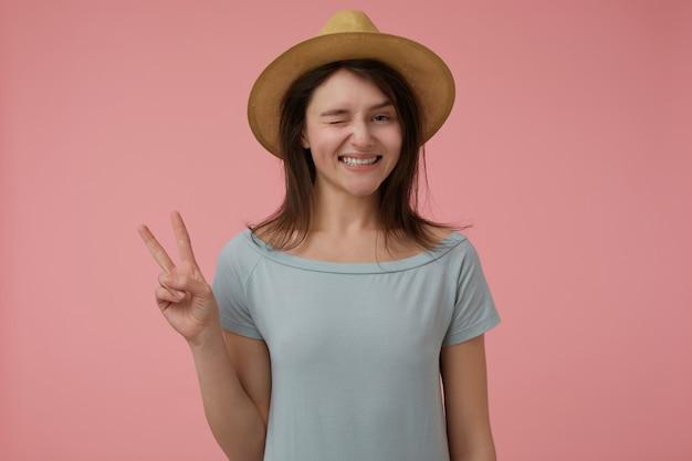 Porträt des attraktiven, erwachsenen mädchens mit dem langen brünetten haar. friedenszeichen und augenzwinkern lächelnd zeigen. trägt ein bläuliches t-shirt und einen hut. isoliert über pastellrosa wand